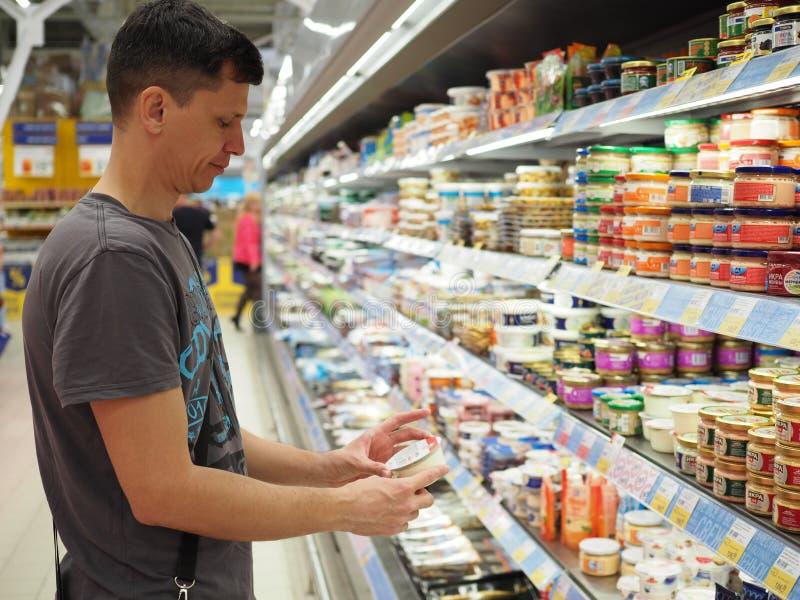 Mann, der choise vom Regal im Supermarkt macht Einkaufswagen mit K?sten und Geld auf einem wei?en Hintergrund Russland, Saratow - stockbilder