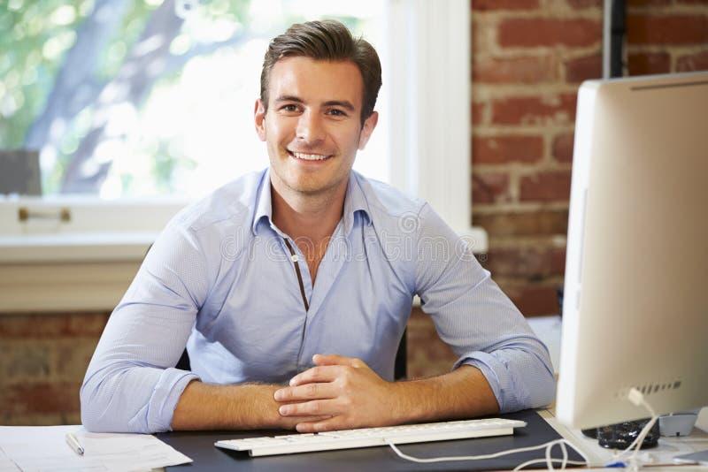Mann, der am Computer im zeitgenössischen Büro arbeitet stockfoto
