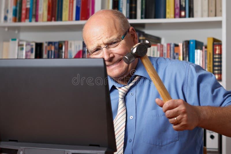 Mann, der Computer mit Hammer schlägt stockbilder
