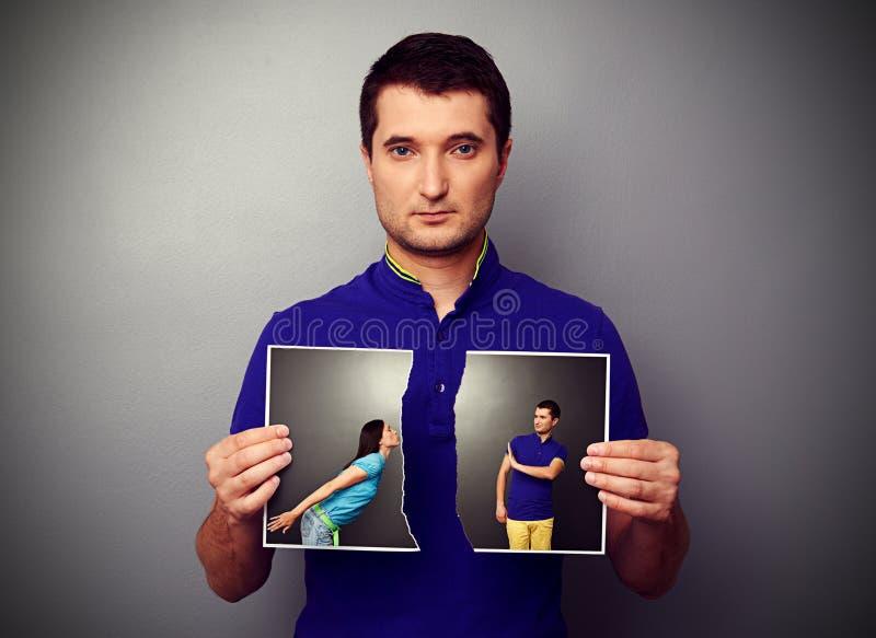 Mann, der das Foto von Paaren zerreißt lizenzfreies stockbild