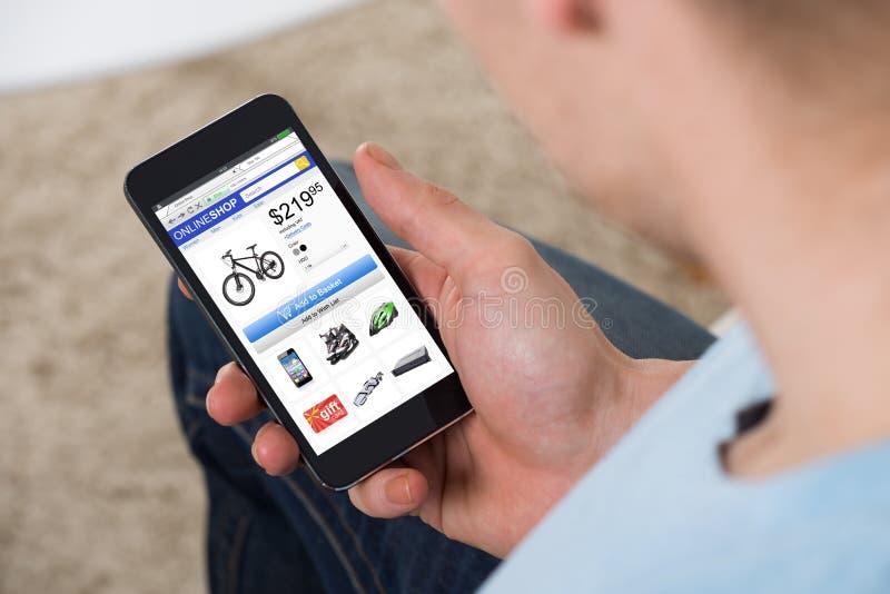 Mann, der das on-line-Einkaufen auf Mobiltelefon tut lizenzfreie stockfotos
