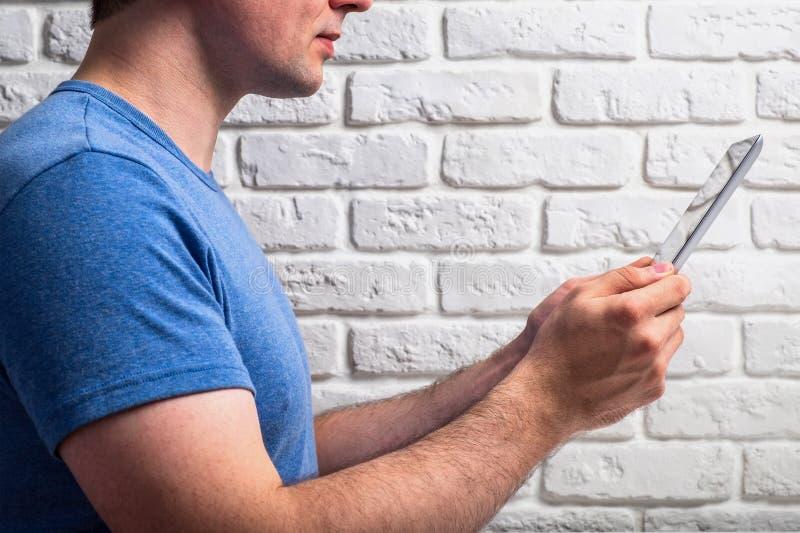 Mann, der das Netz auf seiner Tablette grast lizenzfreie stockfotos