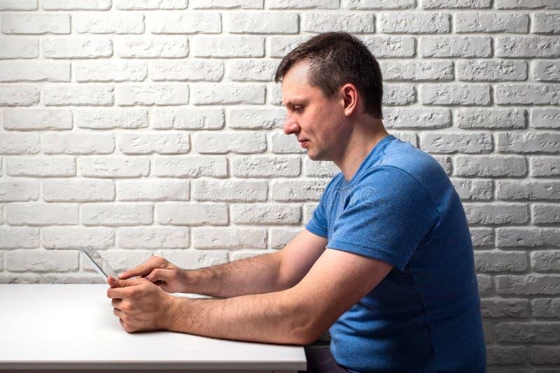 Mann, der das Netz auf seiner Tablette am weißen Tisch grast stockfotos