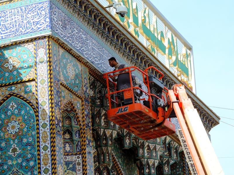 Mann, der das Tor des heiligen Schreins von Abbas Ibn Ali, Kerbela, der Irak säubert lizenzfreie stockfotos