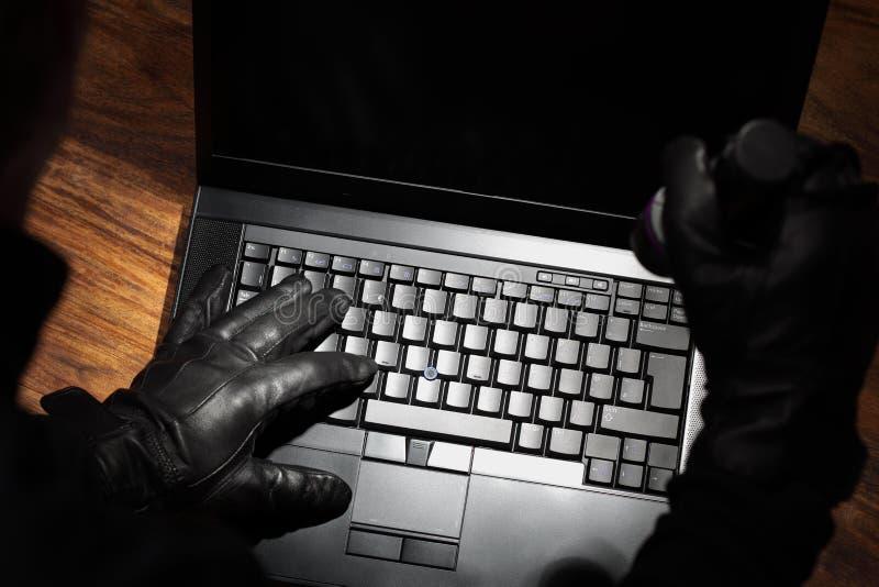 Mann, der Daten von einem Laptop stiehlt stockfotografie