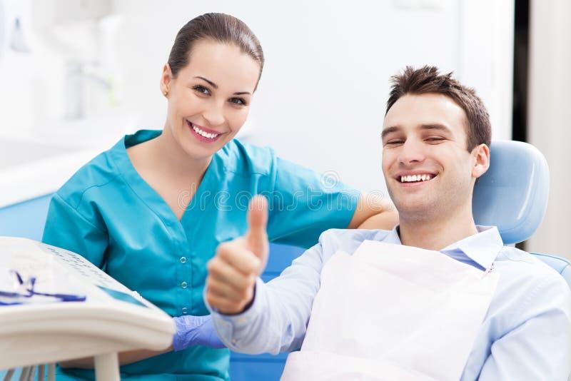 Mann, der Daumen im Zahnarztbüro aufgibt stockbilder