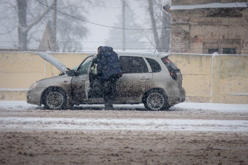 Mann, der defektes Auto auf der Straße in den Schneefällen repariert lizenzfreie stockfotografie