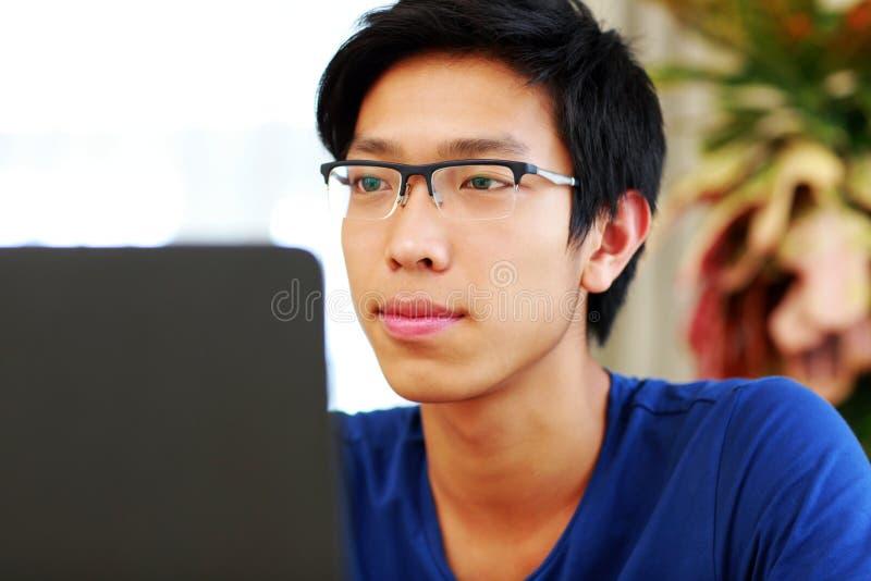 Mann, der an dem Laptop arbeitet lizenzfreie stockbilder