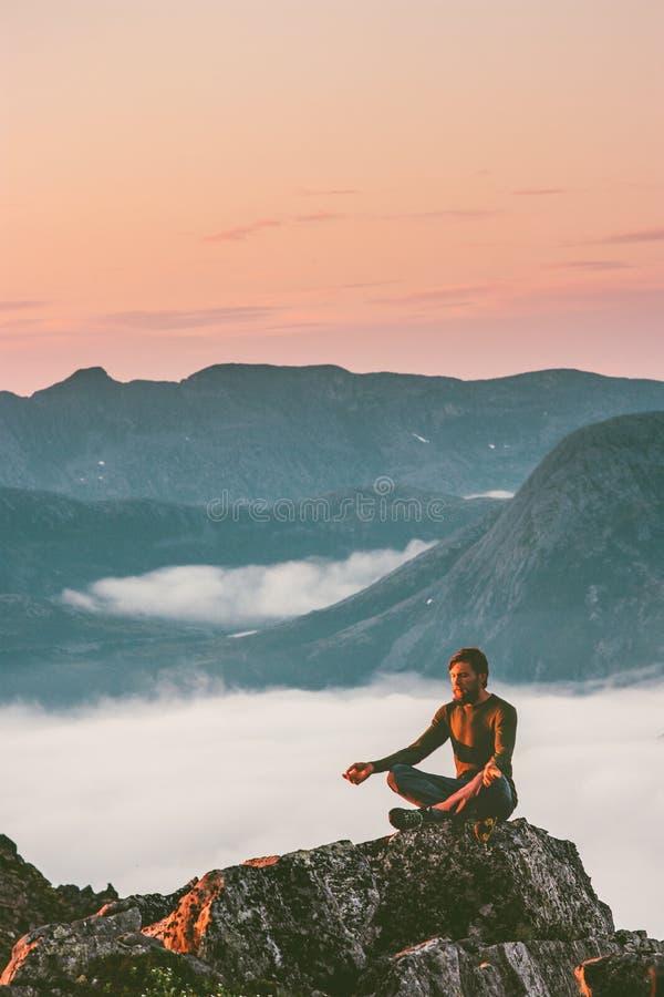 Mann, der in den Bergen allein sich entspannen im Freien meditiert lizenzfreies stockbild
