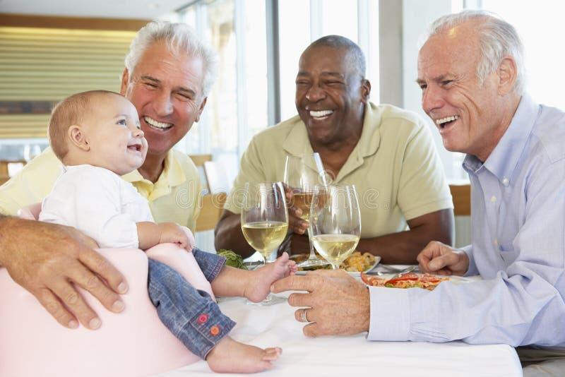 Mann, der den Freunden seine Schätzchen-Enkelin zeigt stockfoto