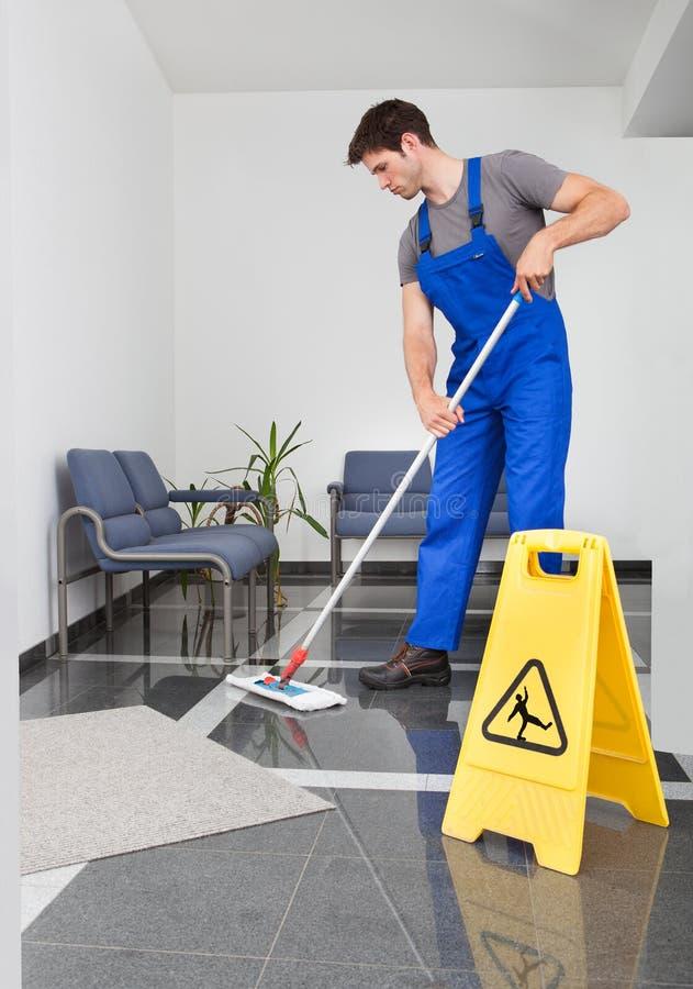 Mann, der den Fußboden säubert lizenzfreie stockbilder
