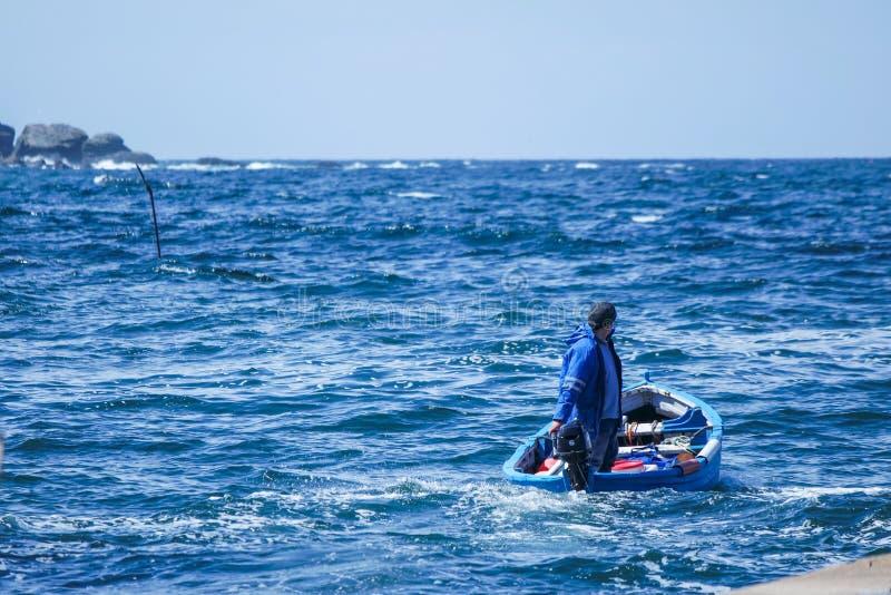 Mann, der den Hafen für die Fischerei verlässt stockfotos