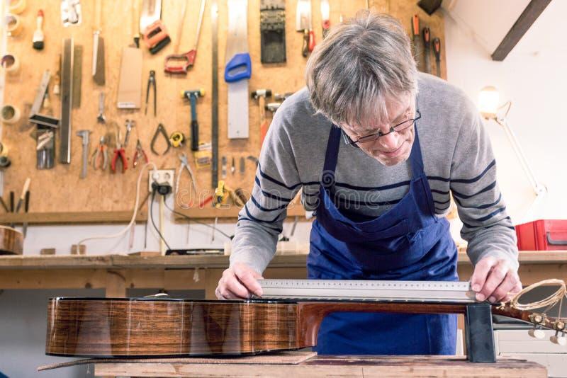 Mann, der den Hals einer Gitarre misst lizenzfreie stockfotografie