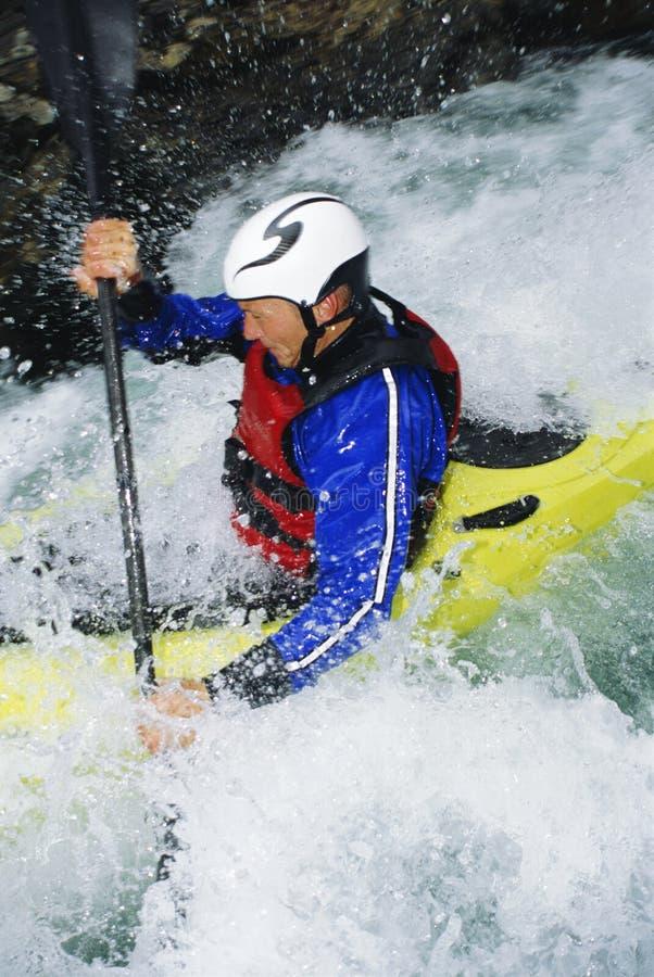 Mann, der in den Rapids kayaking ist stockfoto