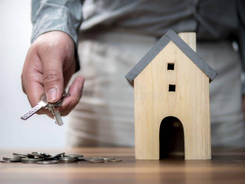 Mann, der den Schlüssel mit Musterhaus hält Rettungsgeldkonzept, Immobilien- und Eigentumskonzept, Haushaltseinsparungen und Fina lizenzfreie stockfotografie