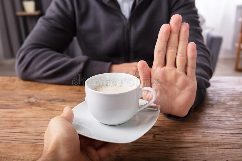 Mann, der den Tasse Kaffee angeboten von der Person ablehnt stockbild