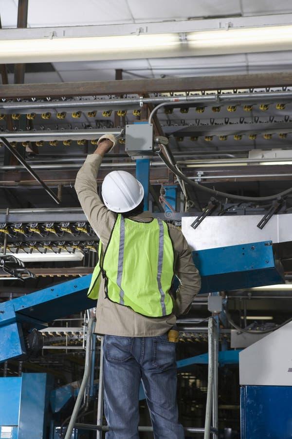 Mann, der in der Druckmaschine-Fabrik arbeitet stockbilder