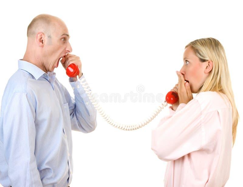 Mann, der an der Frau am Telefon kreischt stockfotos