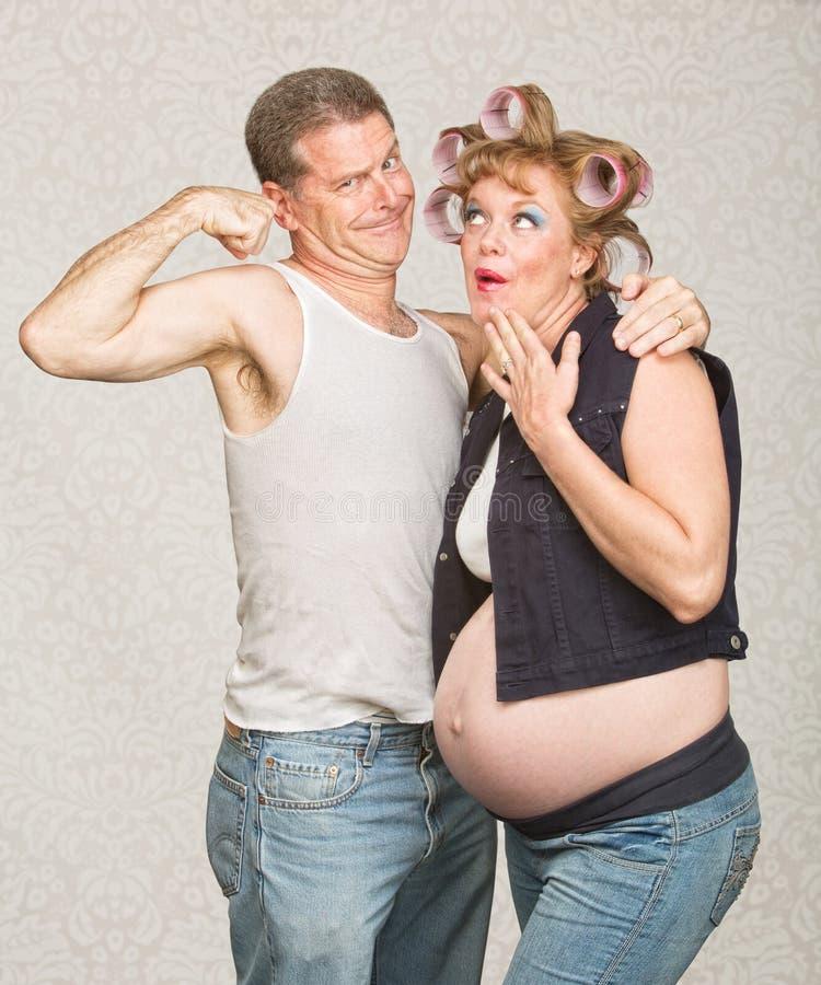 Mann, der der schwangeren Frau Bizeps zeigt stockbild