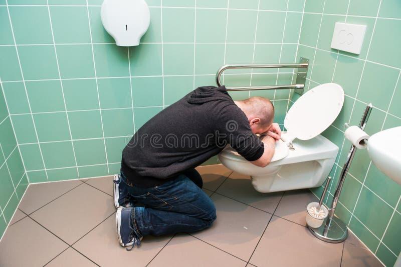 Mann, der in der Toilette sich erbricht stockfoto