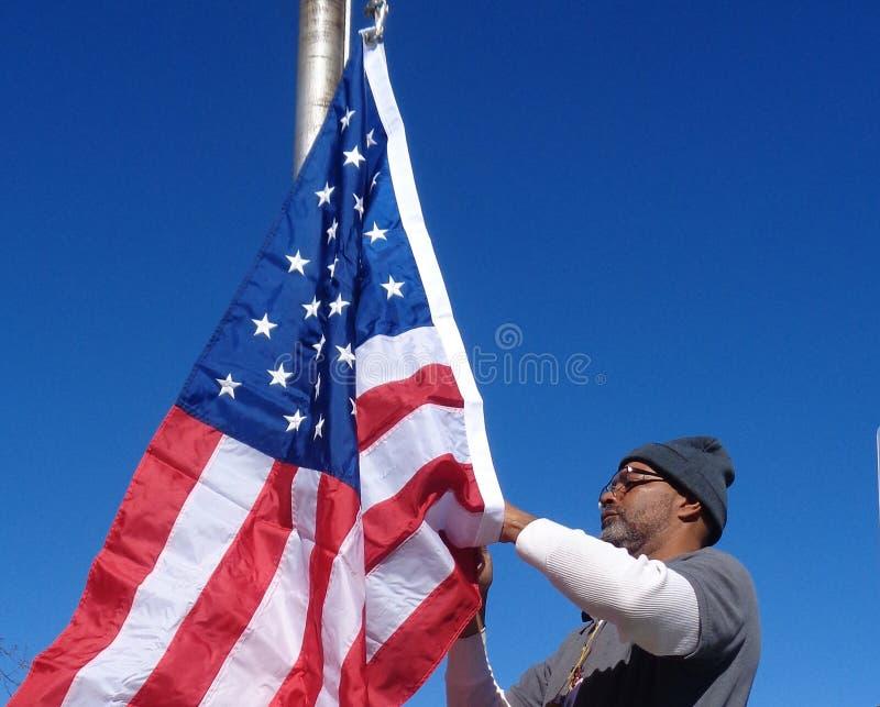 Mann, der die amerikanische Flagge hißt stockbild