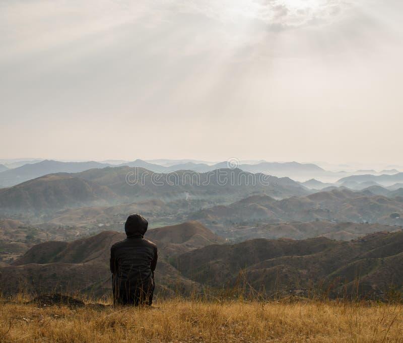 Mann, der die Ansicht in die Hügel genießt stockbilder