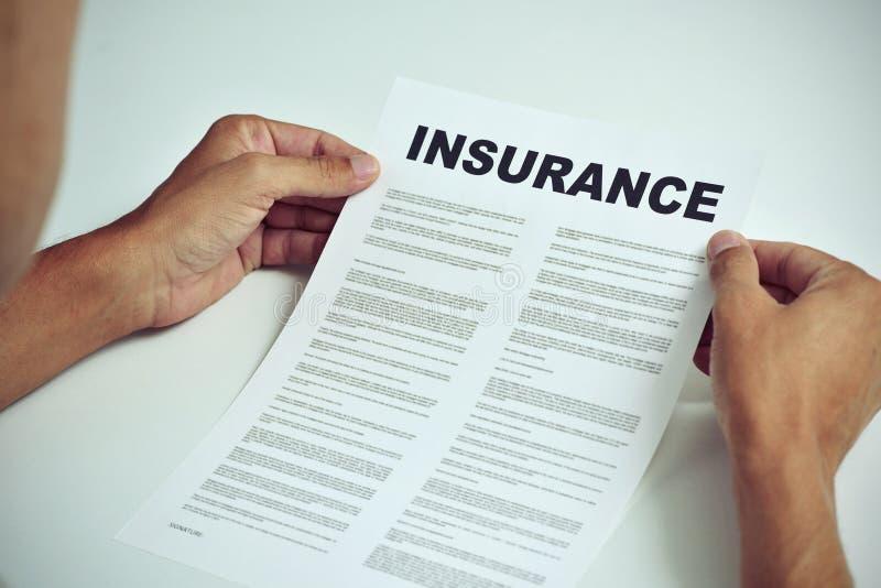 Mann, der die Ausdrücke einer Versicherung liest lizenzfreie stockfotos