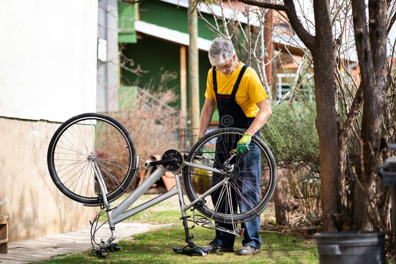 Mann, der die Fahrradkette instandhält während der neuen Jahreszeit schmiert stockfoto