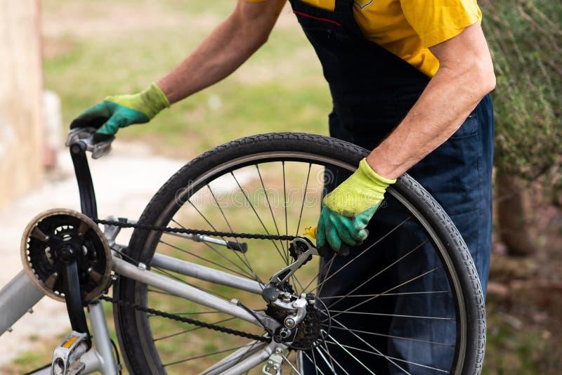 Mann, der die Fahrradkette instandhält während der neuen Jahreszeit schmiert stockfotos