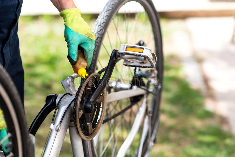 Mann, der die Fahrradkette instandhält während der neuen Jahreszeit schmiert stockfotografie