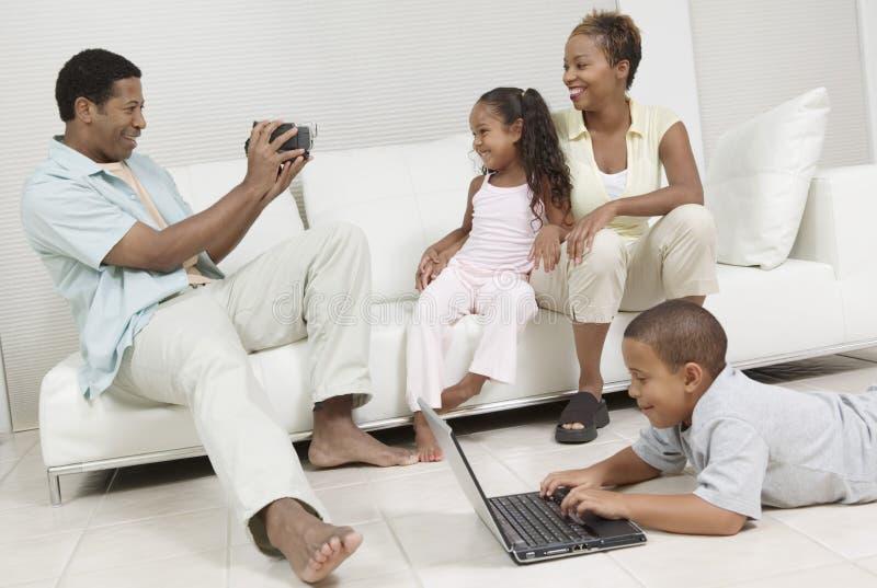 Mann, der die Familie sitzt auf Sofa auf Video aufzeichnet lizenzfreie stockbilder