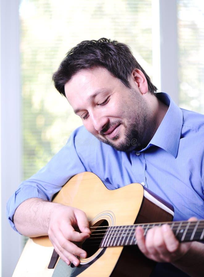 Mann, der die Gitarre Innen spielt stockbild