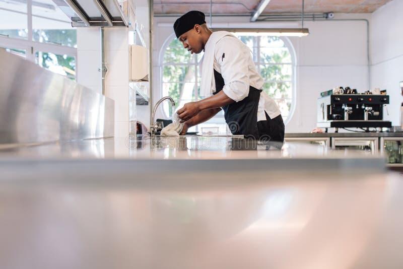 Mann, der die Küchenarbeitsplatte säubert lizenzfreie stockfotos
