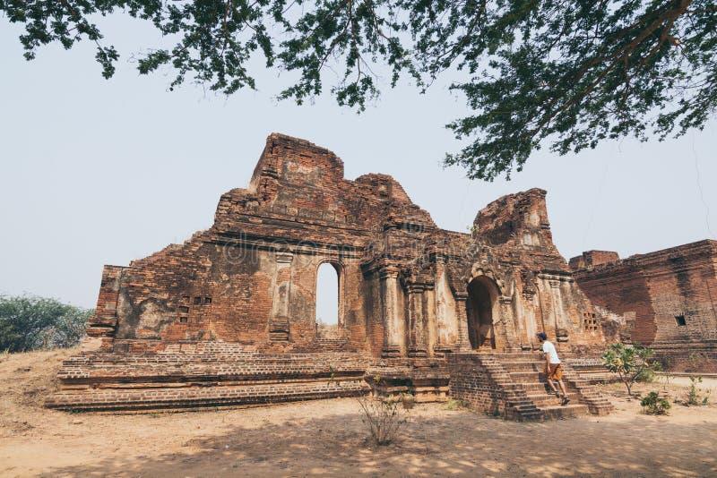 Mann, der die Ruinen des alten Tempels in Bagan, Myanmar anmeldet lizenzfreie stockbilder