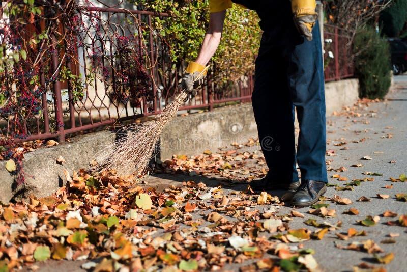 Mann, der die Straße kehrt, um gefallene Blätter zu sammeln stockfoto