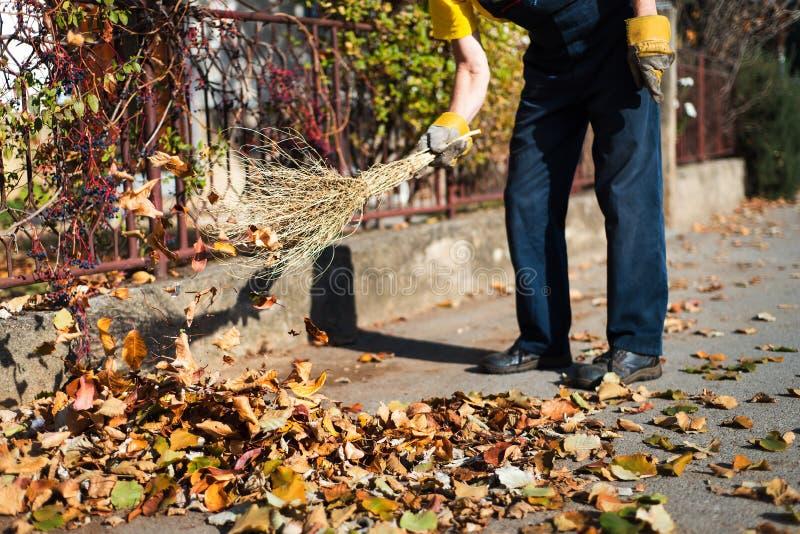 Mann, der die Straße kehrt, um gefallene Blätter zu sammeln lizenzfreies stockbild