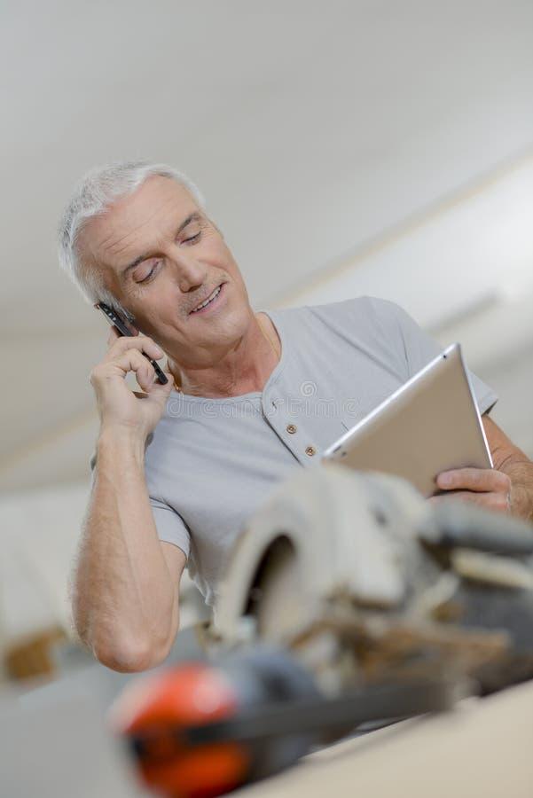 Mann, der die Tablette spricht am Telefon betrachtet stockbilder
