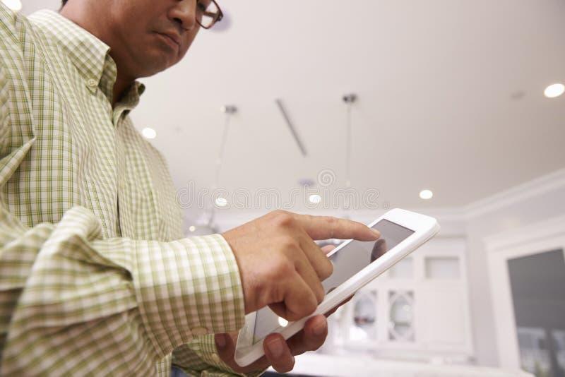 Mann, der Digital-Tablet verwendet, um zu Hause beleuchten zu steuern lizenzfreies stockbild