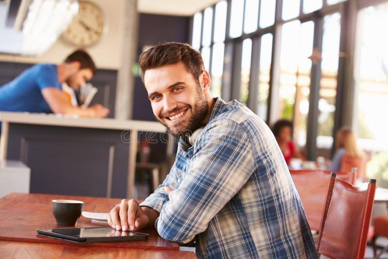 Mann, der digitale Tablette in einer Kaffeestube, Porträt verwendet lizenzfreies stockfoto
