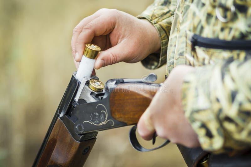 Mann, der doppelläufige Jagdgewehrnahaufnahme auflädt stockfoto