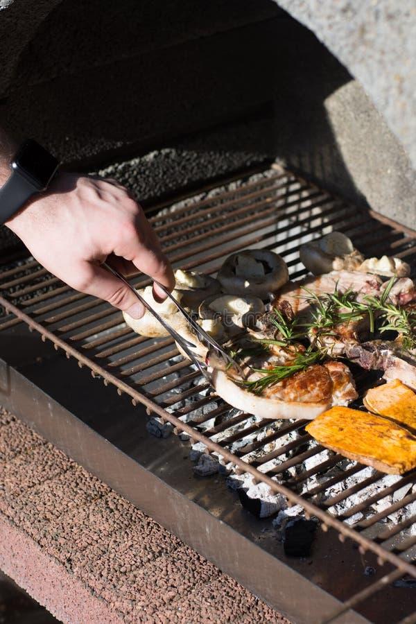 Mann, der draußen bbq-Steaks auf Grill kocht stockbilder