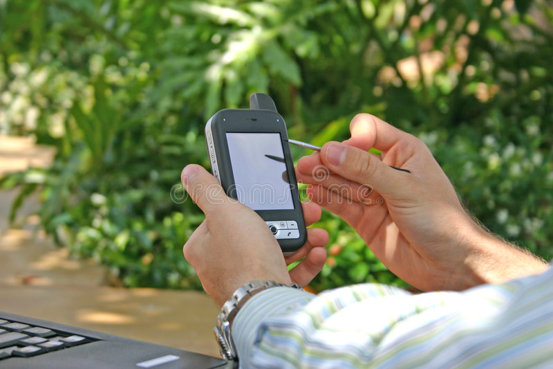Mann, der draußen PDA/Smartphone verwendet stockfoto
