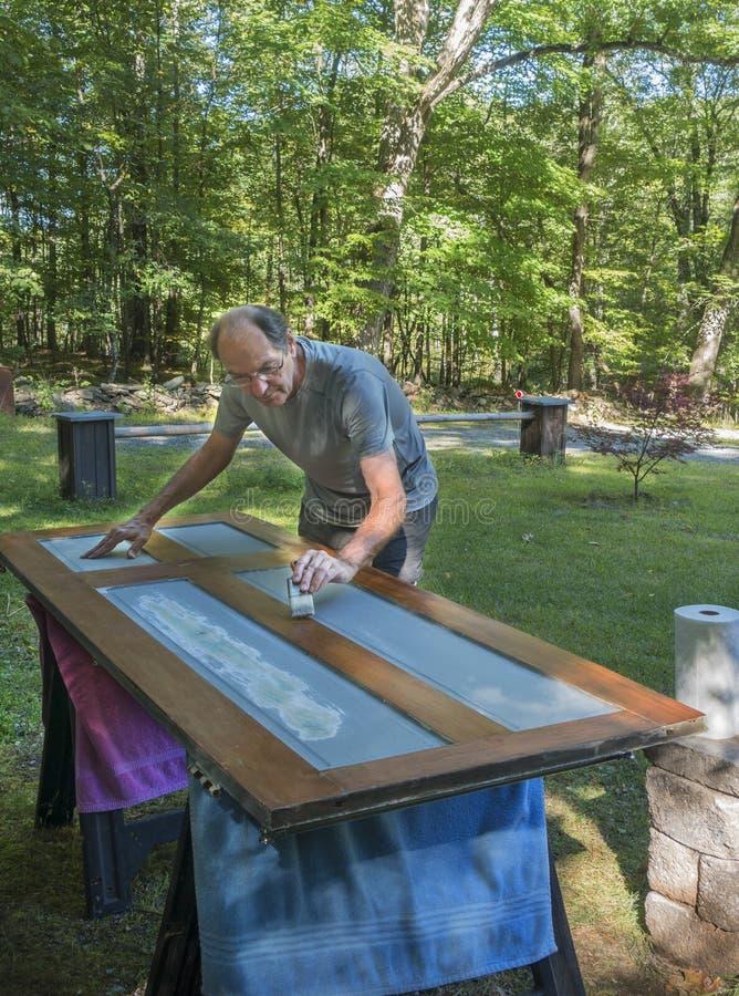 Mann, der draußen Tür malt lizenzfreie stockfotos
