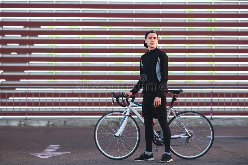 Mann in der dunklen Sportkleidung und mit einem Fahrrad steht auf dem gestreiften Hintergrund der Großleinwand und der Blicke an  stockfotos