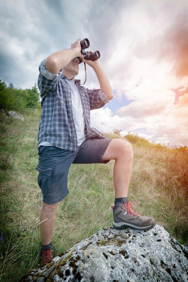 Mann, der durch binokulares schaut lizenzfreie stockfotos