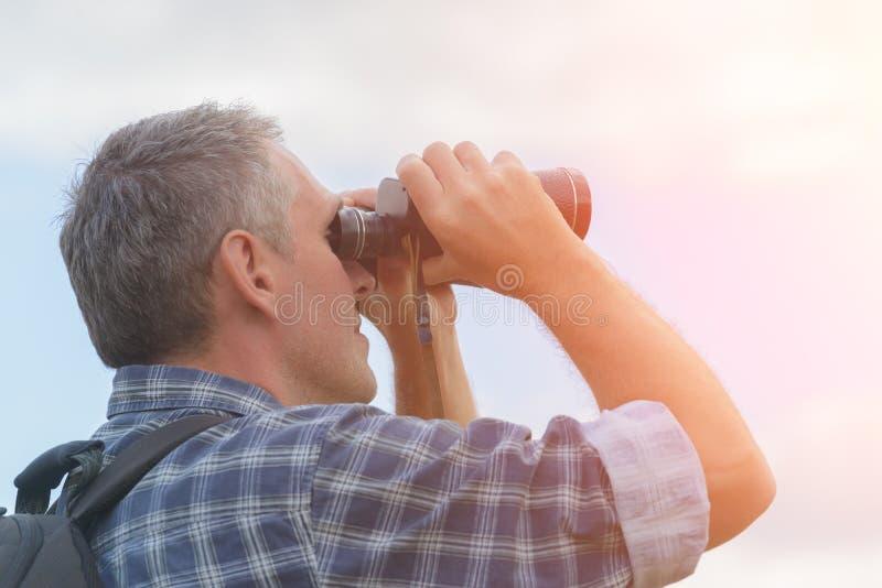 Mann, der durch binokulares schaut stockbilder
