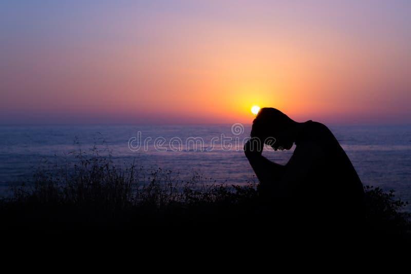 Mann, der durch das Meer bei Sonnenuntergang betet stockfotos