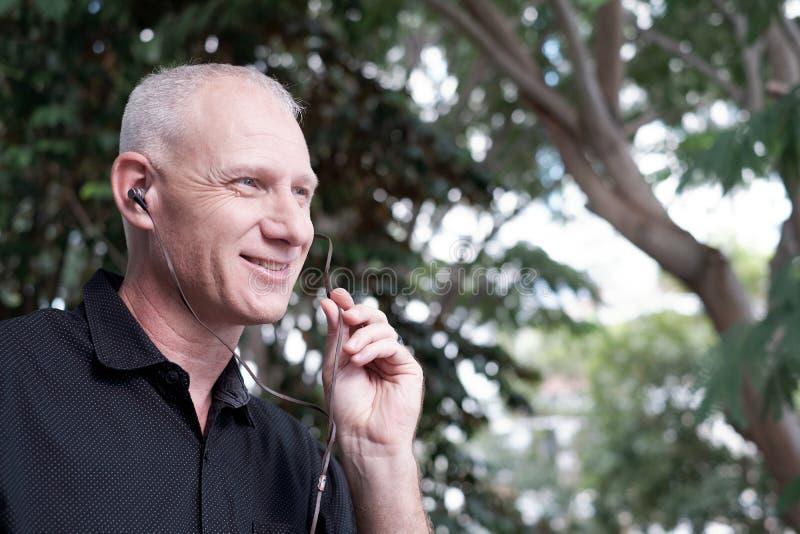 Mann, der durch Earbuds spricht lizenzfreie stockbilder