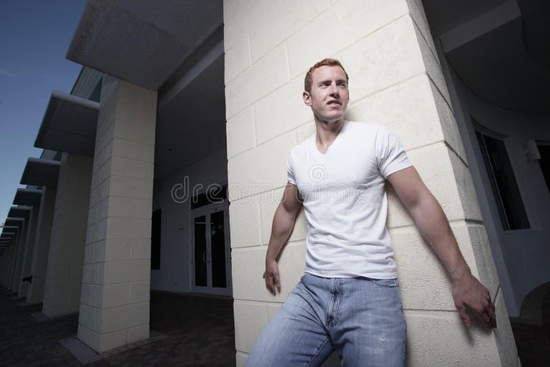 Mann, der durch ein Gebäude aufwirft stockbild