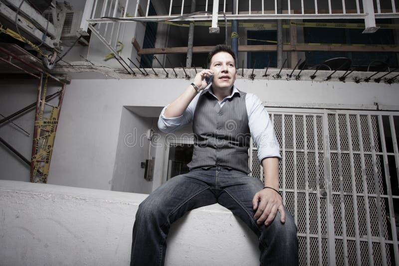 Mann, der durch ein Gebäude im Bau sitzt lizenzfreies stockfoto